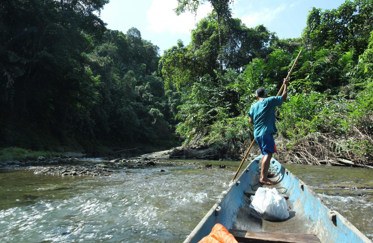 Man navigates his boat through a river in West Sumatra.